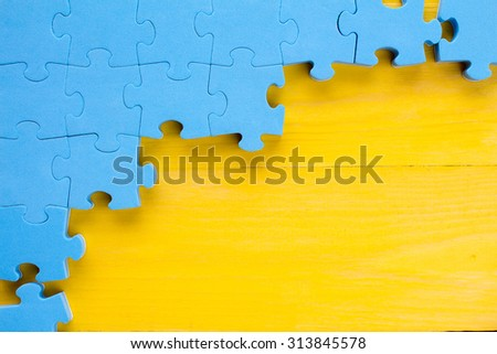 Puzzle on yellow wooden background.Team business concept - stock photo