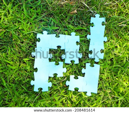 Puzzle pieces on green grass background. Green space concept - stock photo