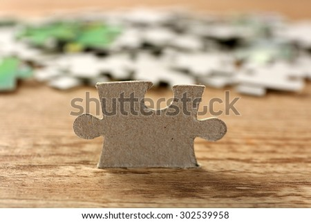 Puzzle pieces on wooden table, closeup - stock photo