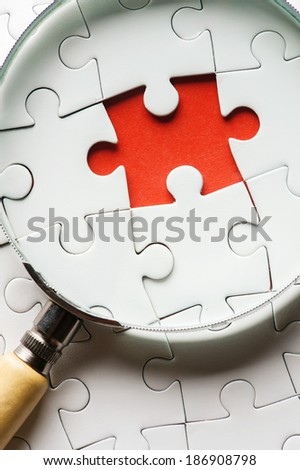 Puzzle pieces with a magnifying glass. Concept image of detecting a defect. - stock photo