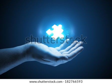 Puzzle Solutions. Conceptual illustration. A man holding a glowing single puzzle piece.