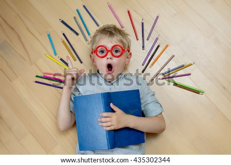 puzzled blonde boy in red shirt in glasses lying on the floor next to the pencil. emotion of surprise, the idea - stock photo