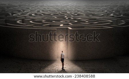 Puzzled businesswoman standing near entrance of labyrinth - stock photo