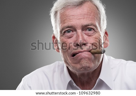 Puzzled senior man on gray background. Studio shot of puzzled senior man with cigar in his mouth - stock photo