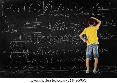 puzzled student looking at a huge blackboard with a difficult equation, school concept