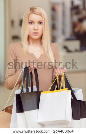Puzzled with the thought. Vertical shot of an attractive blond woman with the puzzled expression of her face holding shopping bags copyspace in her hands  - stock photo