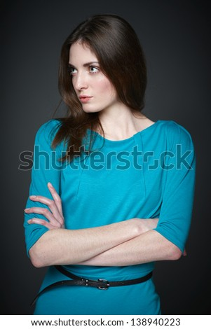 Puzzled woman with folded hands looking away