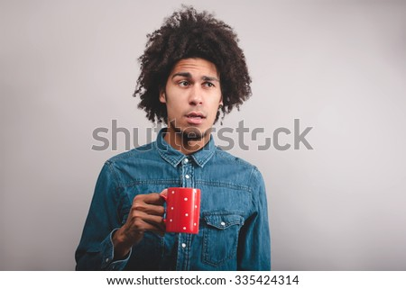 puzzled young man with cup of tea  - stock photo