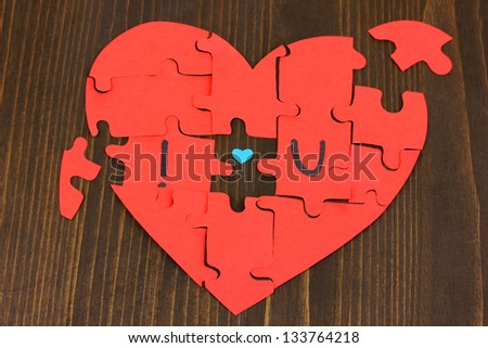 "Puzzles in form of heart with words ""I love you"" on wooden table close-up - stock photo"