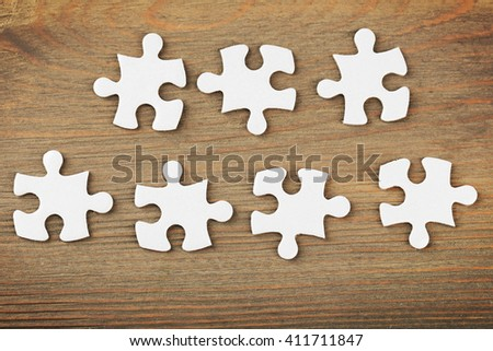 Puzzles on wooden table, closeup