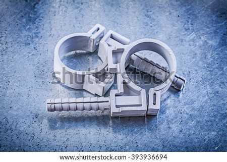Pvc pipe clamps on metallic background construction concept.