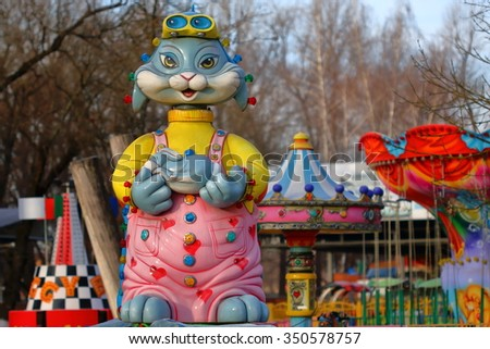 Pyatigorsk, Russia - December 12, 2015: Funny female cat in pink dress keeps in paws a blue rabbit. Detail of the children carousel in City Park.