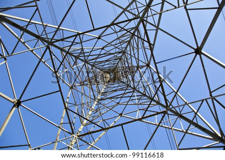 Pylon tower structure viewed from directly below against blue sky