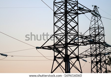 Pylons and transmission power line in sundown