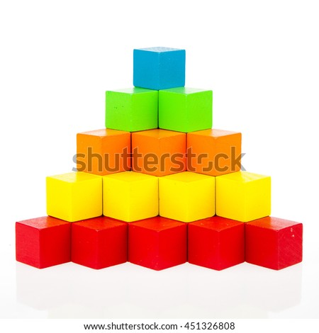 Pyramid build from colored wooden rings with a clown head on top. Toy for babies and toddlers to joyfully learn mechanical skills and colors. Studio shot on white background.