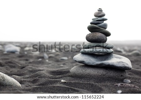 Pyramid from stones on the black sand beach in Iceland. The image close up - stock photo