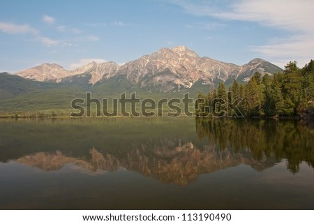Pyramid Lake with Pyramid Island and a mountain reflecting in the quiet waters - stock photo