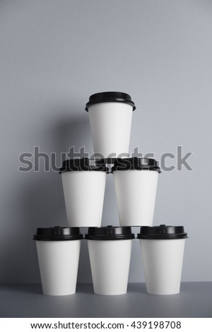 Pyramid made from six white take away paper cups with closed black caps, isolated on simple gray back - stock photo