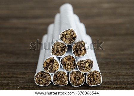 Pyramid of cigarettes on old wood table