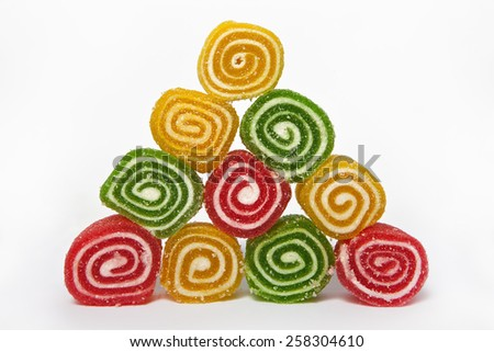 Pyramid of coloured marmalade on white background - stock photo