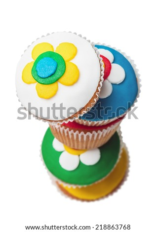 Pyramid of five colorful cupcakes with floral pattern. Focus on the first cupcakes