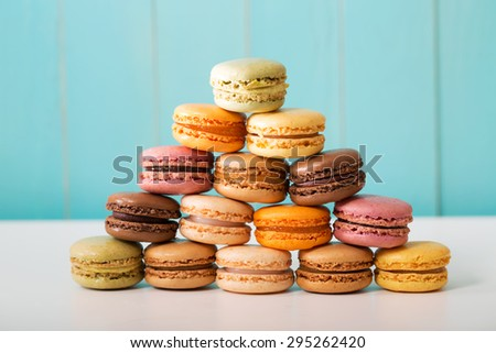 Pyramid of multi-colored macarons on pastel blue wooden background - stock photo
