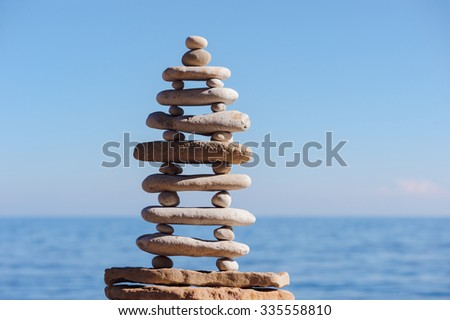 Pyramid of oblong and round pebbles on the seashore - stock photo