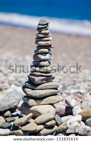 pyramid of stones on the beach - stock photo