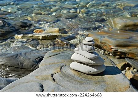 Pyramid of stones zen balance in sea shore - stock photo