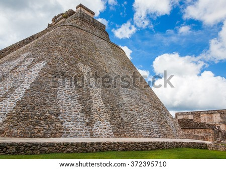 Pyramid of the Magician against the blue cloudy sky - Uxmal, Yucatan, Mexico - stock photo