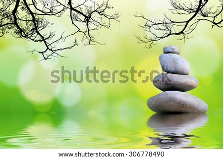 Pyramid of the stones and tree branches or Zen pebbles balance. Spa and healthcare concept. - stock photo