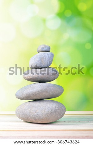 Pyramid of the stones isolated on green bokeh background
