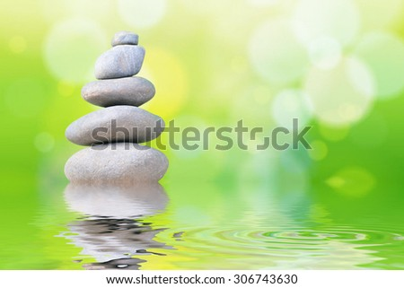 Pyramid of the stones isolated on green bokeh background with reflection water. - stock photo