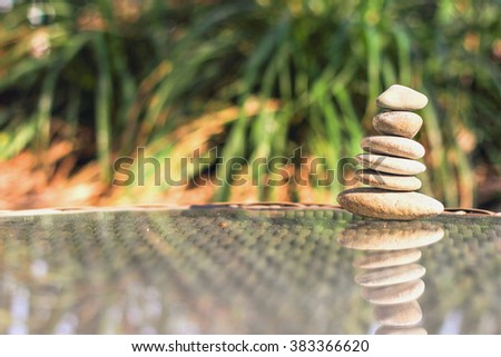 Pyramid of the stones isolated on green natural background - stock photo