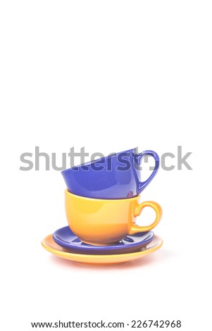 Pyramid of two tea cups of different colors isolated on a white background - stock photo