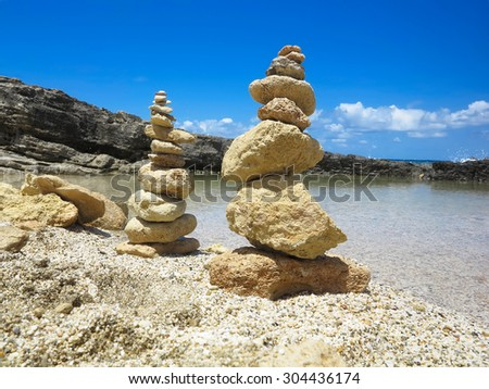 Pyramid stack of zen stones near sea and blue sky background - stock photo
