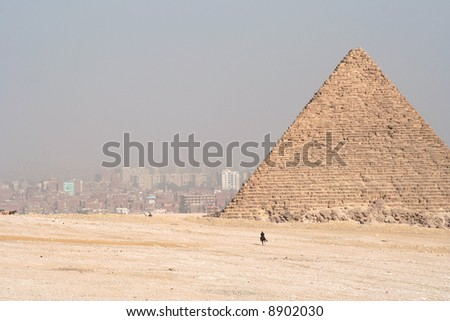 Pyramids in Egypt. Cairo in the background in smog. - stock photo