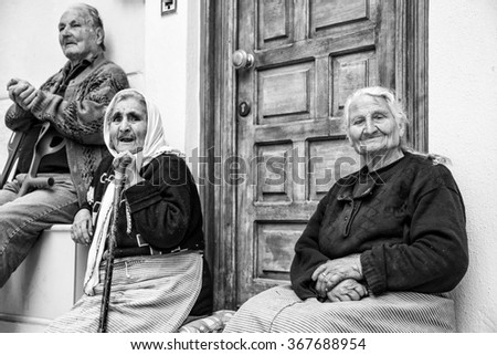 PYRGI, CHIOS ISLAND, GREECE - APRIL 24, 2015; Senior people sitting in front of their house in the Pirgi town of Chios Island in Greece. (Black and white)