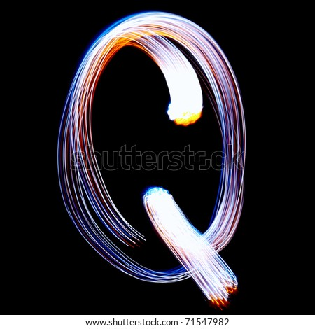 Q - Created by light colorful letters over black background - stock photo