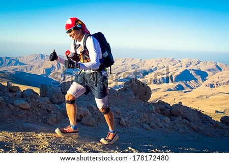 QALHAT, OMAN - JANUARY 28: Unidentified runner running in mountains near Qalhat, on January 28, 2014. Transomania is one of the most extreme marathons, 300 km of mountains and desert. - stock photo