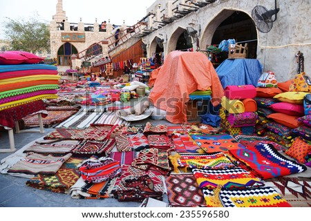 QATAR, DOHA - March 20 2014: Souq Waqif is a main marketplace selling traditional garments, spices, handicrafts, and souvenirs. Colorful garments at the shop in front of Asherg Coffee.. - stock photo