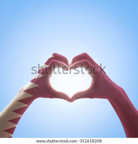 Qatar flag pattern on people hands in heart shape on blue sky background, symbolic sign language expressing love, unity, harmony of people in the country/ nation concept: Happy national day    - stock photo