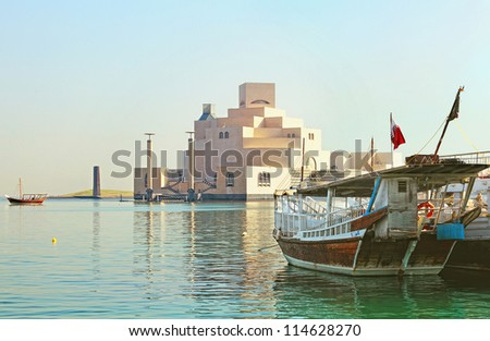 Qatar's museum of Islamic Art on its man-made island beside Doha Corniche, with dhows moored in the bay surrounding it. - stock photo