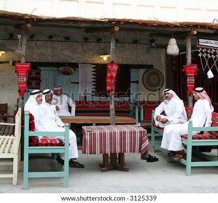 Qatari Arab nationals relaxing at a traditional coffee shop in the Old Souq, Doha, Qatar. The Qatari flag is on the wall. National dress is normal everyday attire for citizens. - stock photo