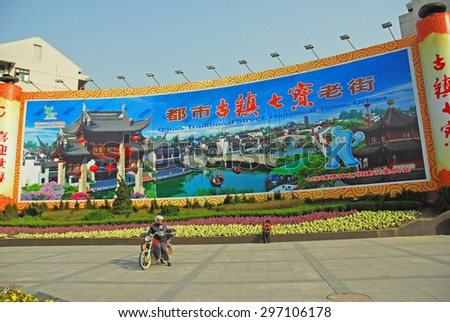 QIBAO, SHANGHAI-MARCH 16, 2010: big poster at the ancient village main entry square. Qibao water village is Shanghai tourist attraction with 1000000 visitors year. - stock photo