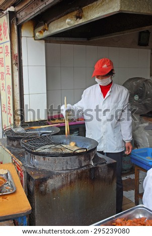 QIBAO, SHANGHAI-MARCH 16, 2010: vendor proposing fried tofu. Qibao water village is Shanghai tourist attraction with 1000000 visitors year. - stock photo