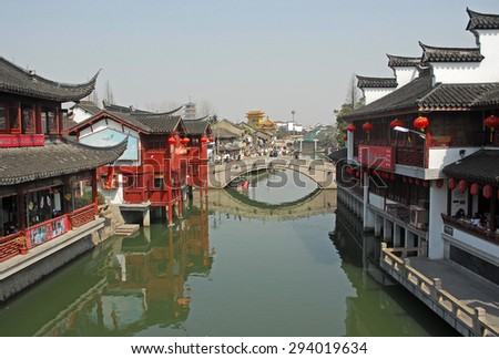 QIBAO, SHANGHAI-MARCH 16, 2010: village canal and old bridge at sunset. Qibao water village is Shanghai tourist attraction with 1000000 visitors year. - stock photo