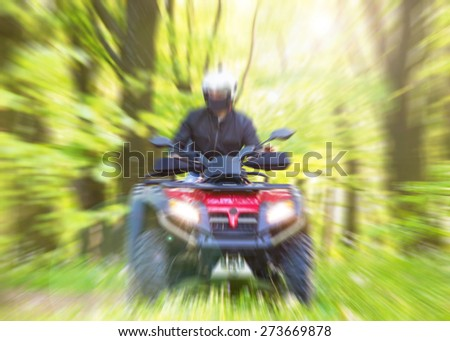 Quad rider going fast cross forrest. Motion blur. Lens flare - stock photo