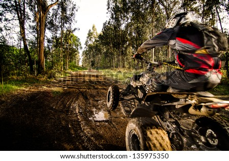 Quad rider jumping on a muddy forest trail. - stock photo