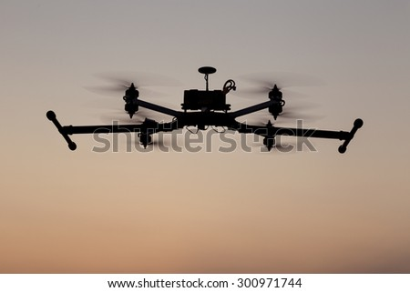 Quadcopter professional drone flying on sunset sky - stock photo